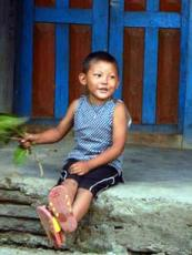 Nepal Lumle Mala Lodge boy with leaves