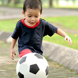 Little boy kicking a soccer ball in Brazil