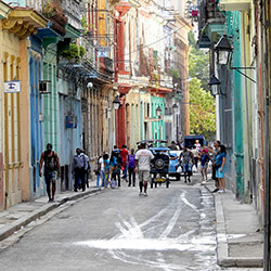 Cuban people walking through Havana's colorful streets.