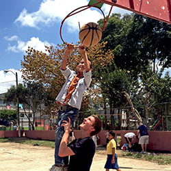 Student playing basketball with children during a mission trip to Guatemala