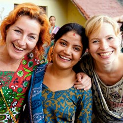 Photograph of a professor and student connecting with a local women during a cultural-immersion program in India.
