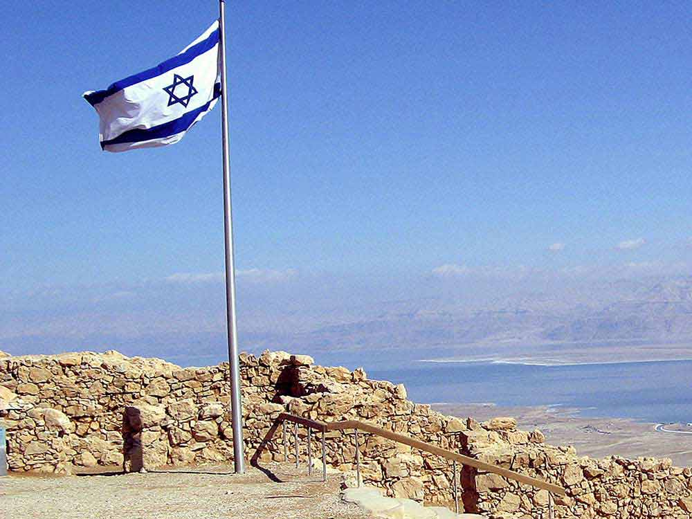 The flag of Israel flying high atop Masada.