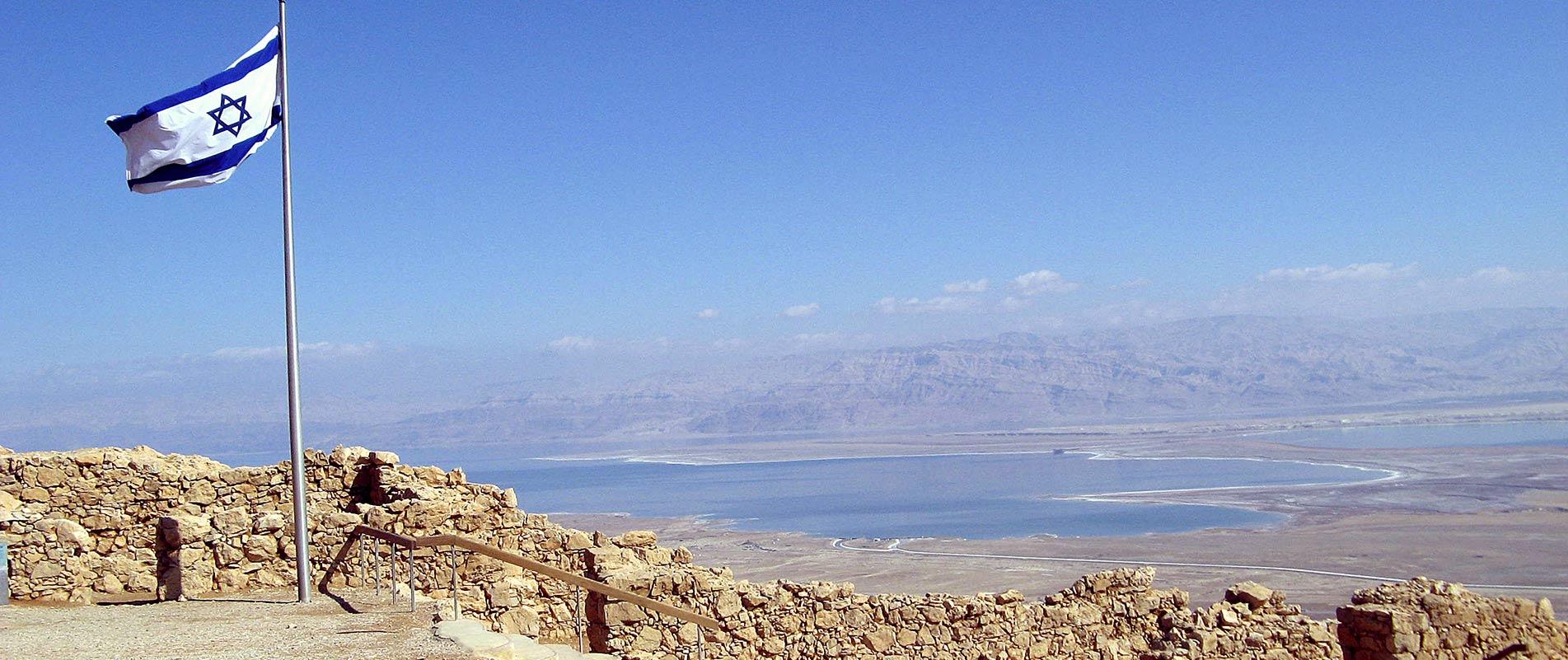 The flag of Israel flying high atop Masada.