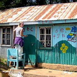 Student using her artistic talents to paint a mural to brighten a local school during a service-learning program in Africa.