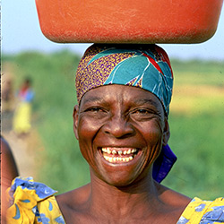 Kenyan woman carrying a bucket on her head