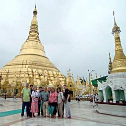 Group of people traveling through Myanmar (formerly Burma ) standing in front of the Shwedagon Pagoda (Also known as the Schwedagon Zedi Daw, the Great Dagon pagoda or the Golden Pagoda), which is one of the most famous pagodas in the world and the main attraction of Myanmar's capital city, Yangon.