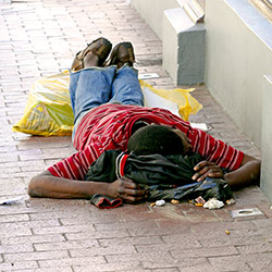 Homeless man laying on the ground in Cape Town, South Africa