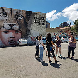 Group meeting in a parking lot with art on the wall behind them.