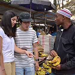 Group talks with a local vendor in Tanzania in a market.
