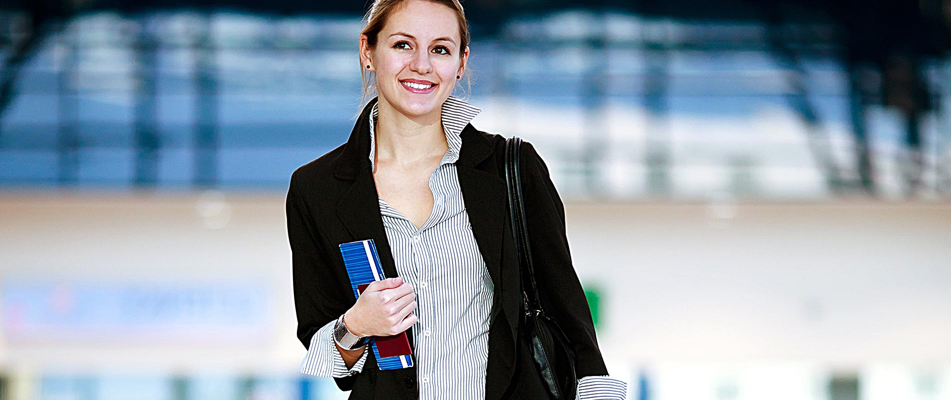 student holding her travel documents in the airport.