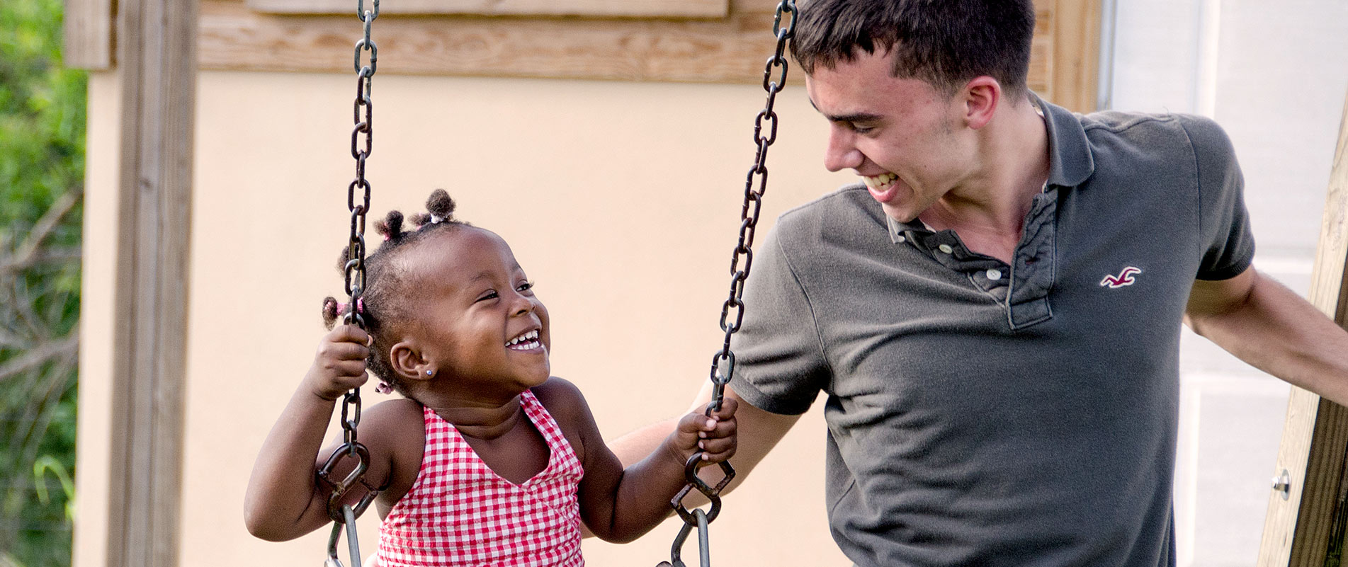 Student volunteer swinging with a local child in Zimbabwe